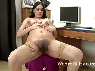 Sexy Riani fingers her hairy pussy on the desk