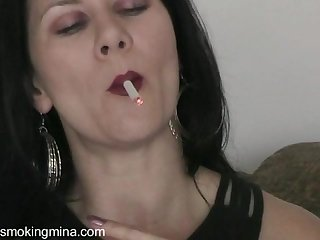 Solo brunette smoking while masturbating using a toy in closeup shoot